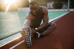 Sporty muscular african male athlete stretching legs. While sitting at the stadium race track Royalty Free Stock Image
