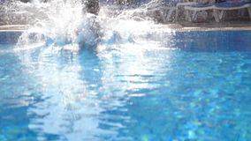 Sporty muscular man jumping in water of basin on sunny day. Young guy swimming in pool. Summer vacation or holiday. Concept. Close up Slow motion stock footage