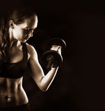 Sporty muscular woman training with dumbbells on black Royalty Free Stock Photo