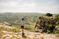Woman in sporty uniform and sneakers is standing on mountains peak stock photos