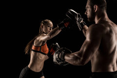 Sporty muscular young man and woman boxing together. Sporty muscular young men and women boxing together isolated on black Royalty Free Stock Images