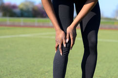 Sporty muscular young woman clutching her knee. Sporty muscular young woman in tights standing on a sports field clutching her knee after injuring her joint stock photography