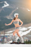 Sporty naked woman is posing on the top of the slope with skis. Wearing boots, helmet and sunglasses Royalty Free Stock Photos