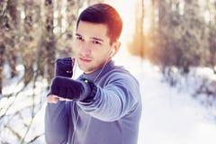 Sporty obsługują robić bokserskiemu ćwiczeniu w lasowej zimie Zdjęcie Stock