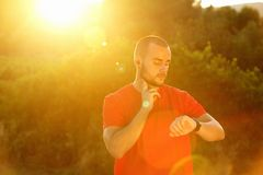 Sporty obsługują sprawdzać puls i patrzeć zegarek zdjęcia stock
