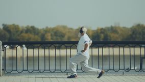 Sporty old man makes lunges near the river