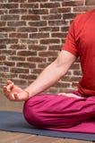 Sporty pamiętający mężczyzna medytuje samotnie na czerwonym ściany z cegieł tle zdjęcia stock