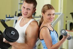 Sporty people. Portrait of sporty couple with dumbbells smiling at camera Royalty Free Stock Photos