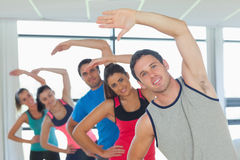 Sporty people doing power fitness exercise at yoga class Royalty Free Stock Image