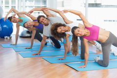 Sporty people doing stretching exercises in fitness studio Royalty Free Stock Images