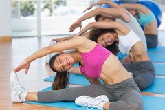 Sporty people doing stretching exercises in fitness studio Royalty Free Stock Image