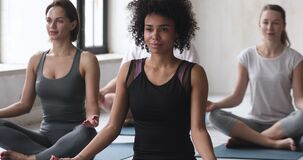 Sporty people group seated in lotus pose meditating together indoors