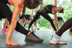 Sporty people group training with fitness instructor on pilates classes. Sports workout background. Back view of women legs in sneakers. Group of sporty people royalty free stock photography