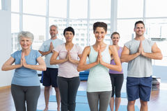 Sporty people with joined hands at fitness studio Royalty Free Stock Photos