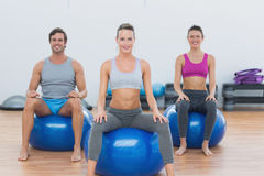 Sporty people sitting on exercise balls at gym Royalty Free Stock Photo