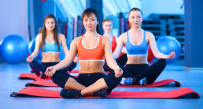Sporty people sitting on exercise mats at a bright fitness studio Stock Image