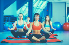 Sporty people sitting on exercise mats at a bright fitness studio Royalty Free Stock Photography
