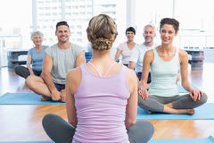 Sporty people sitting on exercise mats at fitness studio Stock Image
