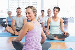 Sporty people sitting on exercise mats at fitness studio Royalty Free Stock Images