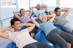 Sporty people stretching on exercise balls Royalty Free Stock Photo
