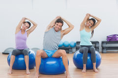 Sporty people stretching hands on exercise balls at gym Stock Photography