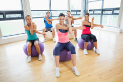 Sporty people stretching hands on exercise balls at gym Royalty Free Stock Images