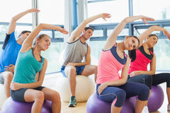 Sporty people stretching hands on exercise balls at gym Royalty Free Stock Photography
