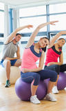 Sporty people stretching hands on exercise balls at gym Stock Photo