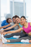 Sporty people stretching hands to legs in fitness studio Royalty Free Stock Photos