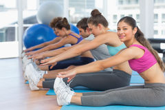 Sporty people stretching hands to legs in fitness studio Royalty Free Stock Photography