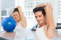 Sporty people stretching hands at yoga class Stock Images