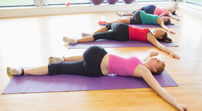 Sporty people stretching on mats at yoga class Stock Images
