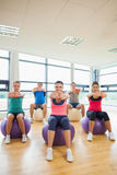 Sporty people stretching out hands on exercise balls at gym Stock Photo