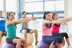 Sporty people stretching out hands on exercise balls at gym Stock Image