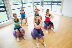 Sporty people stretching out hands on exercise balls at gym Royalty Free Stock Photo