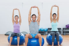 Sporty people stretching up hands on exercise balls at gym Royalty Free Stock Photo