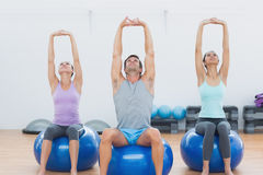 Sporty people stretching up hands on exercise balls at gym Stock Image