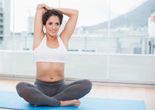 Sporty pleased brunette stretching on exercise mat Royalty Free Stock Image