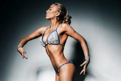Sporty posing beautiful woman in blue bikini Royalty Free Stock Photos