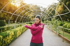 Sporty pregnant woman stretching arms in autumn outdoor. Fitness pregnant woman doing stretching exercise for arms and shoulder outdoor at urban park on early Royalty Free Stock Photography