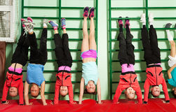 Sporty preteen kids holding handstand in gym Stock Images