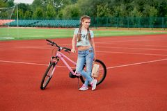 Sporty pretty teen girl loves sports.Teenage girl relaxing on a stadium. Stock Image