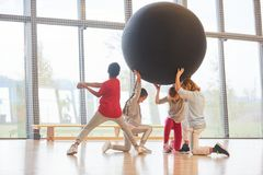 Students raise a huge ball in teamwork. Sporty pupils raise a huge ball in the gym in teamwork Royalty Free Stock Photo