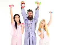 Sporty regime concept. Man in robe, trainer holds clock, attractive young women in pajamas doing exercises with. Dumbbells, bodybuilder, good healthy, lifestyle Royalty Free Stock Image