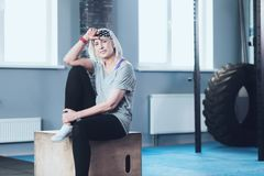 Sporty retired woman relaxing on wooden box at gym. Joyful retired life. Relaxed elderly lady in sportswear chilling on a fitness box and smiling after taking Stock Photo