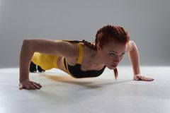 Sporty rude woman doing push-ups. On white background Stock Photos