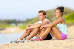 Sporty runners resting sitting before run on beach. Running athletes couple men and women taking a break after jogging. Fit sport fitness couple living healthy Royalty Free Stock Photography