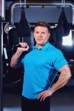 Sporty samiec z ciężarami dumbbells w jego ręka gym Obraz Royalty Free