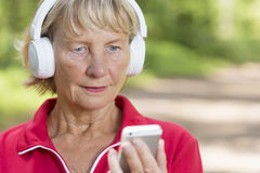 Sporty senior jogger woman listening music from phone Stock Photography