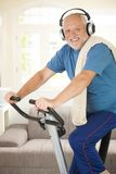 Sporty senior listening to music while exercising. Sporty senior listening to music via headphones while exercising on stationary bike, at home, smiling at Stock Photos